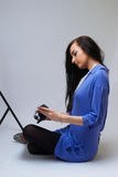 Young woman with camera. Young happy woman holding small video camera.at white background Stock Image
