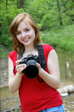 Young woman with camera near river Stock Images