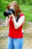 Young woman with camera near river Stock Photos