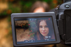 Young woman on camera screen looking at camera Stock Images