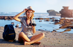 Young woman with camera. Sea vacation and hobby. Pretty young woman with camera and rucksack on the ocean beach Stock Photos