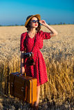 Young woman with camera and suitcase Stock Images