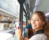 Young woman on the camera from the window of the tourist bus Royalty Free Stock Photos