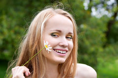 Young woman with camomile. Beautiful young woman with camomile, summer day Royalty Free Stock Photos
