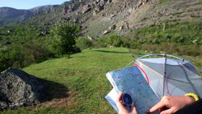 Young woman in camp with map and compass looks at the mountains and search path. stock video