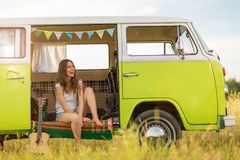 Young woman enjoying a road trip. Young woman in a camper van, smiling Royalty Free Stock Images