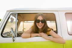 Young woman enjoying a road trip. Young woman in a camper van, smiling Stock Photo