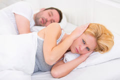 Young woman can't sleep because of boyfriend's snoring stock photography
