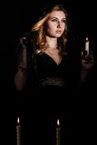 Young woman with a candle in darkness stock photography