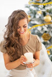Young woman with candle near christmas tree Stock Photography