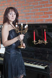 Young woman with candlestick stands near the piano. Beautiful young woman with candlestick stands near the piano Stock Image
