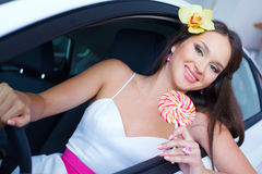Young woman with candy with New car Royalty Free Stock Image
