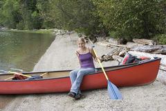 Young woman in a canoe holding the paddle Stock Image