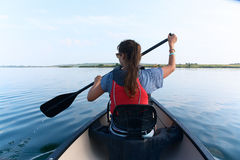 Young woman canoeing in the lake on a summer day. Young lady with long straight brunette hair in sunglasses and life vest paddling the kayak, canoeing in the stock photography