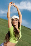 Young woman in cap with arms raised Stock Photo