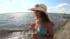 The girl in the hat drinks juice by the water. A young woman in a cap drinks orange juice on beach by the river stock video