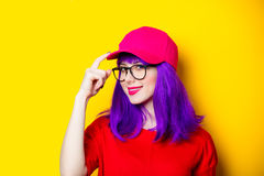 Young woman in cap and glasses. Portrait of beautiful smiling young woman in cap and glasses on the wonderful yellow studio background Royalty Free Stock Photography