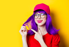 Young woman in cap and glasses. Portrait of beautiful smiling young woman in cap and glasses on the wonderful yellow studio background Royalty Free Stock Images