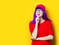 Young woman in cap and glasses. Portrait of beautiful young woman in cap and glasses on the wonderful yellow studio background Royalty Free Stock Images