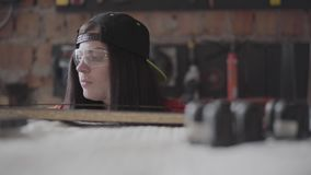 Young woman in a cap and protective glasses with pierced lip and ring in nose measuring length of the MDF plate with the. Young woman in black cap and protective stock video footage