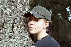 Young woman with cap and tree. Young woman with cap and a big tree stock image