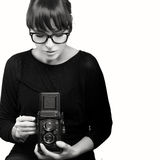 Young Woman Capturing Photo Using Vintage Camera. Attractive Young Woman Wearing Black Clothes and Glasses Capturing Photo Using Vintage Camera. Monochrome royalty free stock photos