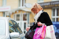 Young woman with shopping bags at the car Stock Photos