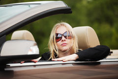 Young fashion woman in sunglasses driving convertible car Stock Photography