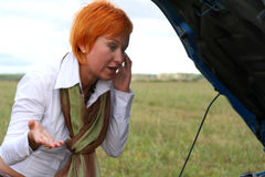 Young woman with car. Young red-haired woman with her broken car with mobile phone. The girl have a big problem Royalty Free Stock Images