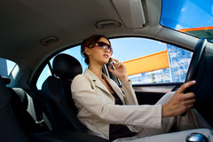 Young woman in the car. A young woman driving a car and phoning Royalty Free Stock Photography
