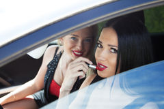Young woman in the car applying lipstick Royalty Free Stock Photography