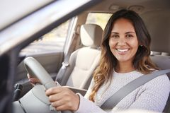 Young woman in car driving seat looking to camera, portrait stock photo