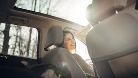 Young woman in a car,female driver looking at the passenger and smiling.Enjoying the ride,traveling,road trip concept.Driver. Feeling happy and safe.Learning Stock Image