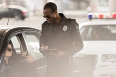 Young woman in car giving driver license to african american policeman with clipboard. And pen stock photo