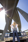 Young woman by car with hands on hips beneath overpass, low angle view (sun flare) Royalty Free Stock Image