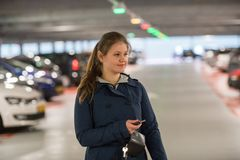 Woman in parking garage. Young woman with car keys in parking garage looking for a car royalty free stock photo