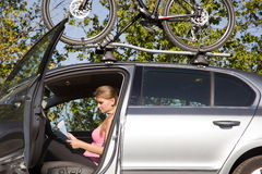 Young woman in a car with a map in hand Royalty Free Stock Photos