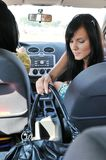 Young woman in car reaching handbag Royalty Free Stock Photo