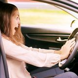 Young woman in car. Ride instruction accident. Automobile loan royalty free stock photo