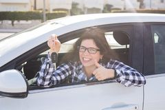Young woman in car shows thumbs up and key royalty free stock photo