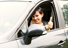 Young woman in the car with thumb up Royalty Free Stock Image