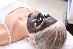 Young woman with carbon nanogel on her face in salon. Peeling procedure Stock Photos