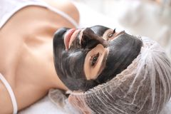 Young woman with carbon nanogel on her face. In salon. Peeling procedure Stock Image