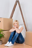 Young Woman With Cardboard Boxes Sitting On Hardwood Floor Royalty Free Stock Photos