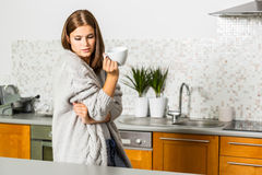 Young woman in cardigan with mug of hot tea. In kitchen Royalty Free Stock Photography
