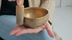 Young woman in cardigan relaxing with nepal singing bowl. Close up shot of nepal singing bowl in woman`s hand. Meditation and relax concept stock video
