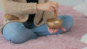 Young woman in cardigan relaxing with nepal singing bowl stock video footage