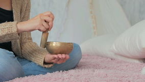 Young woman in cardigan relaxing with nepal singing bowl stock video