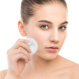 Young woman cares for face skin. Cleaning perfect fresh skin using cotton pad. Isolated. Royalty Free Stock Images