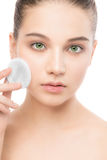 Young woman cares for face skin. Cleaning perfect fresh skin using cotton pad. Isolated. Stock Photo
